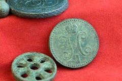 Eine kupferne alte russische Münze und ein rundes Rad auf einem roten Hintergrund, Gegenstände des 18. Jahrhunderts Lizenzfreie Stockbilder
