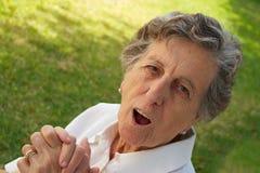 Eine lächelnde alte Frau drückt ihr Gefühl des Seins astonishe aus Lizenzfreies Stockfoto