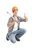 Eine lächelnde Arbeitskraft, die eine BauWasserwaage und ein Geben anhält Lizenzfreie Stockbilder
