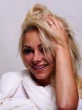 Eine lächelnde blonde behaarte Frau untersucht die Kamera Stockbild