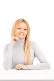 Eine lächelnde blonde Frau, die auf einer Tabelle aufwirft Stockfotografie
