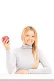 Eine lächelnde blonde Frau, die einen roten Apfel auf einer Tabelle anhält Stockbilder