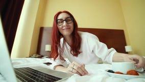 Eine lächelnde Frau des Ingwers, die auf dem Bett liegt und mit einem Laptop - freiberuflich tätiger Job arbeitet stock video