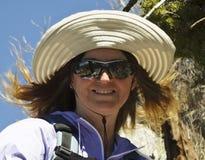 Eine lächelnde Frau, die mit dem Windblown Haar wandert Stockfoto