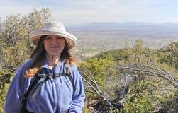 Eine lächelnde Frau, die mit dem Windblown Haar wandert Lizenzfreie Stockfotografie