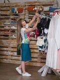Eine lächelnde Frau, die sexy Unterwäsche in einem Kleidungsshop sich wählt Eine Frau mit kleiden auf einem unscharfen Hintergrun Lizenzfreie Stockfotos