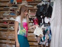 Eine lächelnde Frau, die sexy Unterwäsche in einem Kleidungsshop sich wählt Eine Frau mit kleiden auf einem unscharfen Hintergrun Stockfoto