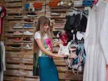 Eine lächelnde Frau, die sexy Unterwäsche in einem Kleidungsshop sich wählt Eine Frau mit kleiden auf einem unscharfen Hintergrun Stockbilder