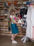 Eine lächelnde Frau, die sexy Unterwäsche in einem Kleidungsshop sich wählt Eine Frau mit kleiden auf einem unscharfen Hintergrun Lizenzfreie Stockbilder