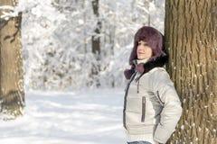 Eine lächelnde Frau steht im Wald, der einen Pelzhut trägt und Stockfotografie