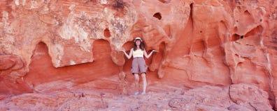 Eine lächelnde Frau und eine Sandstein-Klippe Stockbilder