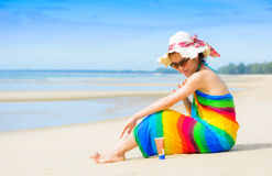 Eine lächelnde Frau wendet sunblock nahe dem Meer an Stockbilder
