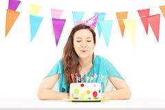 Eine lächelnde Geburtstagsfrau mit einem Parteihut, der die Kerzen O durchbrennt Lizenzfreie Stockfotos