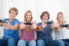 Eine lächelnde Gruppe der Freunde, wie sie die Kamera während Spiel betrachten Stockbild