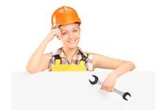 Eine lächelnde weibliche Arbeitskraft, die einen Schlüssel anhält   Stockbilder