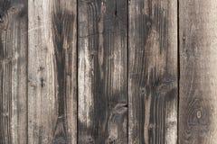 Eine ländliche alte Wand von den schwarzen und braunen hölzernen Planken mit einem Kratzer beunruhigte Patina Lizenzfreie Stockbilder
