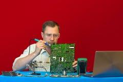 Eine lötende elektronische Schaltung des Mannes Ingenieur-Service-Center repariert das Stromversorgung LCD-Fernsehen Stockbild