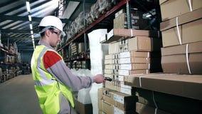 Eine Lagerarbeitskraft in der Schutzausrüstung benutzt einen Strichkodescanner stock video footage