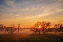 Eine Landschaft des Herbstes und des nebeligen Landschaftsgreenfield mit Dorf auf einem Hintergrund bei Sonnenuntergang Lizenzfreie Stockfotos
