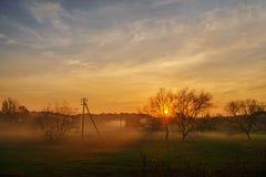 Eine Landschaft des Herbstes und des nebeligen Landschaftsgreenfield mit Dorf auf einem Hintergrund bei Sonnenuntergang Lizenzfreies Stockbild