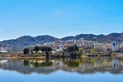 Eine Landschaft einer Stadt, die in das Rückhaltebecken sich reflektiert lizenzfreies stockfoto