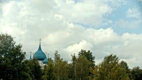 Eine Landschaft von Spitzen von Bäumen des Waldes und von blauen Spitzen der Kirche stock footage