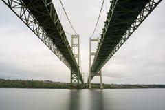 Eine lange Belichtung der Tacoma-Engebrücke von darunterliegend am Flussuferstrand lizenzfreie stockfotos