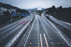 Eine lange Belichtung schoss von beweglichen Autos während des Sonnenaufgangs Lizenzfreie Stockfotografie
