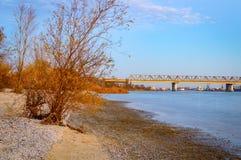 Eine lange Eisenbahnbrücke über dem Fluss Ansicht vom Ufer bei Sonnenuntergang Lizenzfreie Stockbilder