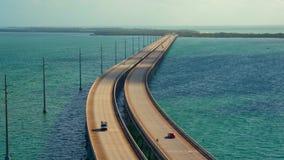 Eine lange Straßenbrücke, die den Ozean mit dem Verkehr bewegt beide Richtungen kreuzt stock video