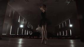 Eine langsam tanzende Ballerina vor Scheinwerferlichtern Einige Scheinwerfer zeigen eine tanzende Ballerina in einem dunklen Stad stock footage