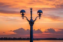 Eine Laternen-Ansicht während des Sonnenuntergangs auf der Ufergegend über dem Fluss Stockbilder