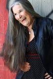 Eine laut lachende ältere Frau mit dem langen grauen Haar Lizenzfreies Stockfoto