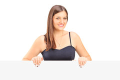Eine lächelnde junge Frau, die hinter einem Panel aufwirft Stockbild