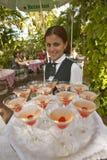 Eine lächelnde kubanische Frau, die einen Behälter von Getränken am touristischen Restaurant in Havana Cuba anbietet Lizenzfreies Stockfoto