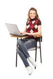 Eine lächelnde Studentenfrau, die an einem Laptop gesetzt auf einem Stuhl arbeitet Stockbild