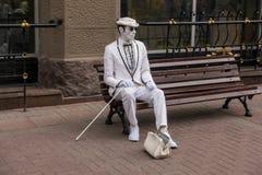 Eine lebende Statue eines Straßenkünstlers, der auf einer Bank sitzt lizenzfreie stockbilder