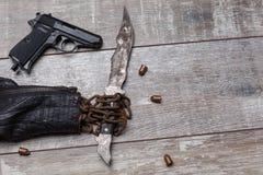 Eine Lederjacke vom Ärmel, eine alte Kette ist, in der es ein rostiges Messer gibt, als Nächstes dort ist eine Pistole sichtbar Stockfotografie