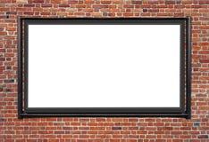 Eine leere Anschlagtafel angebracht zu einer Gebäudeäußer-Backsteinmauer lizenzfreie stockbilder