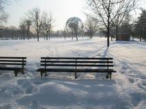 Eine leere Bank bedeckt durch Schnee stockbild