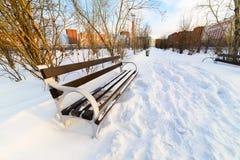 Eine leere Bank im schneebedeckten Stadtpark. Stockfoto