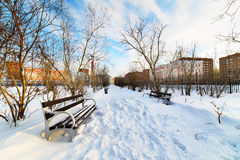 Eine leere Bank im schneebedeckten Stadtpark Stockbild