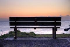 Eine leere Bank am Sonnenaufgang Lizenzfreie Stockfotos