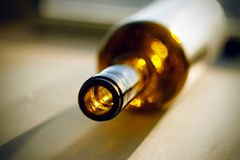 Eine leere Flasche Alkohol, liegt auf der sonnenbeschienen Oberfläche stockbild