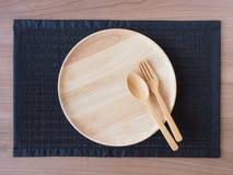 Eine leere hölzerne Platte mit hölzernen Löffeln und Gabeln Stockfoto