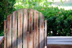 Eine leere Holzbank im grünen Garten mit Sonnenlicht lizenzfreie stockfotografie