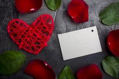 Eine leere Karte für eine Unterzeichnung unter den Blüten einer Rose und des roten Herzens auf einem dunklen Hintergrund Valentin Lizenzfreie Stockfotografie