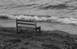 Eine leere Sitzbank auf Strand über Wellen Stockfotos