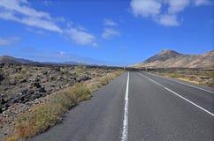 Eine leere Straße durch vulkanische Landschaft von Lanzarote Stockbild