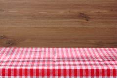 Eine leere Tabelle mit einer roten karierten Tischdecke Hölzerner Hintergrund Lizenzfreie Stockfotografie